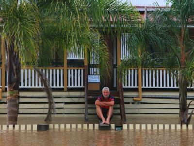 Man sitting on stairs in flood