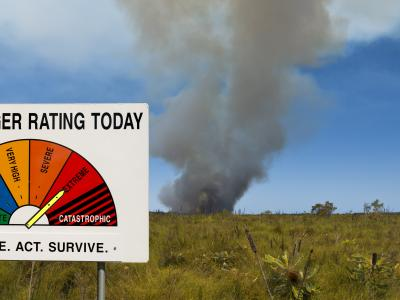 Fire danger sign with bushfire in background