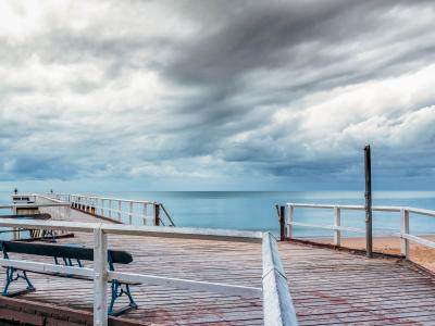 Pier on beach with stormy sky