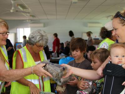 Volunteers handing ration pack to community member