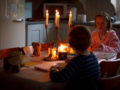 The power has gone out and two children are sitting together at a table at home with candles in front of them for light