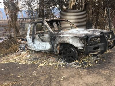 Burnt out ute next to water tank