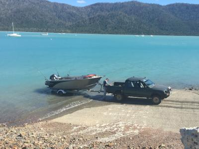 Man hitching boat to ute at boat ramp